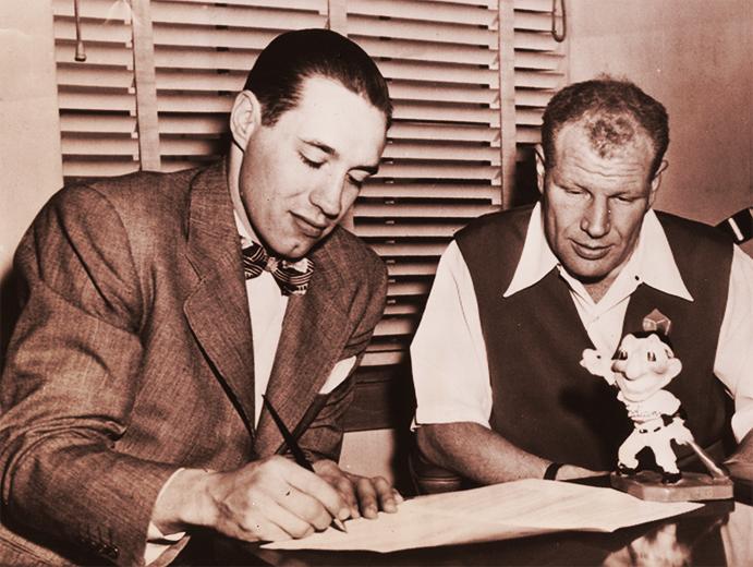 Bob Feller signs a contract for Bill Veeck