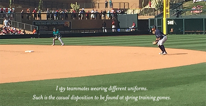 Teammates on field wearing different uniforms during spring training